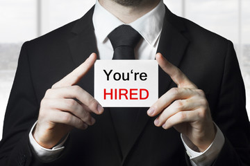 businessman holding sign you are hired