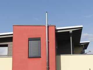Modernes Passivhaus mit roter Fassade und Sonnenschutz