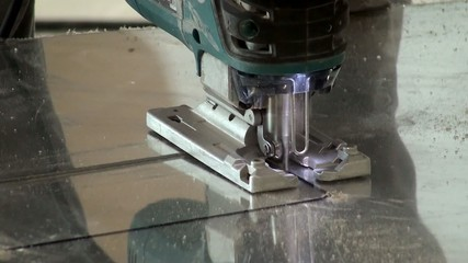 Sawing mirrored plastic using an electric jig saw. Closeup.
