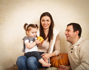 Happy smiling family with pumpkin indoor