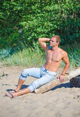 Muscular attractive man resting on the beach.