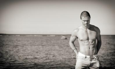 Muscular attractive man posing near the sea.