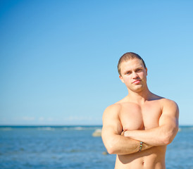 Muscular attractive man posing near the sea.