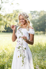 Attractive blonde in the field holding flower in hand