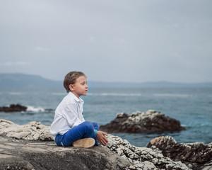 Little boy sitting calm on the solitade sea beach