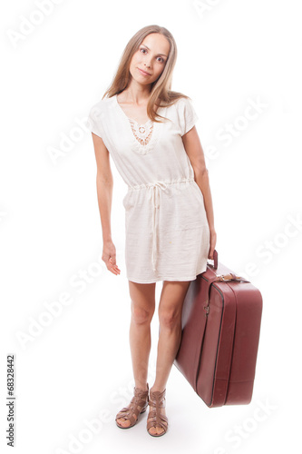 Girl standing with suitcase. Isolated on white