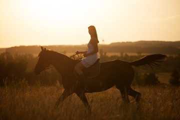 Girl on a horse at sunset