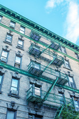 Classic New York Bowery building with green ladders for fire esc