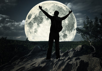 man standing on the top of mountain looking at the moon