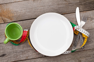 Plate with measure tape, cup, knife and fork. Diet food