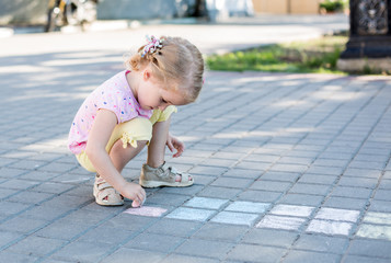 cute little girl drawing with chalk