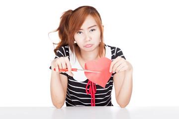 Unhappy Asian girl cut heart shape paper