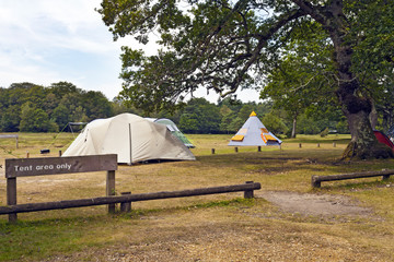 Big family tents and tepee in a camping ground under trees