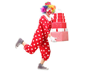 Male clown running and holding presents
