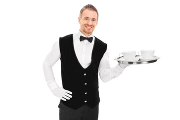 Male butler holding a tray with two cups of coffee