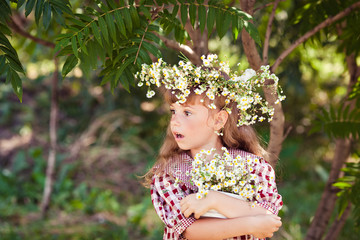 Child girl with daisies and wreath on head