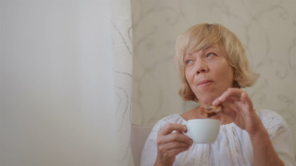 Senior woman sitting by the window drinking tea