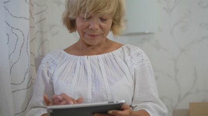 Senior woman using computer tablet at home