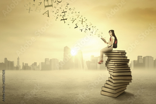 Student sitting on books outdoors