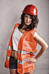 Sexy girl in safety helmet and orange vest