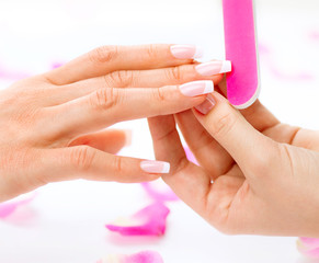 Woman in a beauty salon receiving a manicure by a beautician