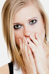 Surprised afraid girl covering mouth with hand