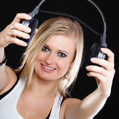 Beautiful girl holding headphones on black