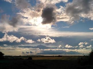 Sun breaking through clouds over fields