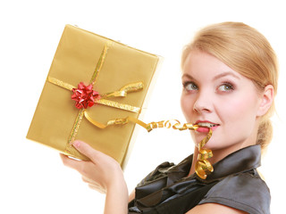 Blond girl with golden christmas gift box ribbon in teeth. Holid