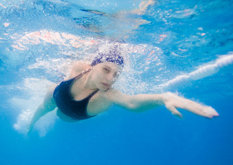 Young woman swimming the front crawl in a pool, taken underwater
