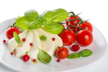 mozzarella cherry tomatoes basil on a white plate