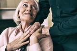Senior woman on wheelchair taking her husband