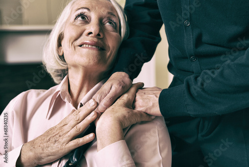 Senior woman on wheelchair taking her husband's hand - 68340235