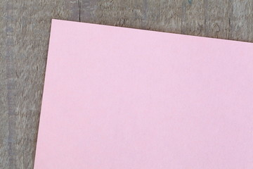Blank pink note paper on wooden background