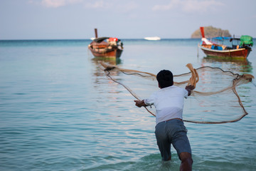 throwing fishing net on beach in Thailand