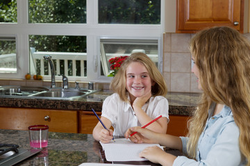 Sisters doing their homework while in the kitchen