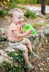 happy toddler boy drinks water
