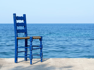Blue chair by the sea in Greece