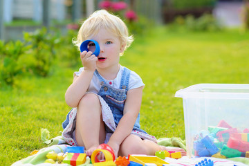 Happy toddler girl playing with colorful plastic toys outdoors