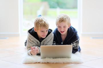 Two school boys doing homework using laptop