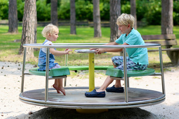 Brother and sister having fun in summer park at playground