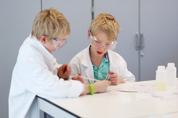Two school boys having chemistry lesson in the lab