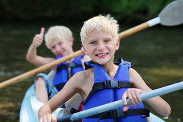 Two happy boys enjoying kayak on the river