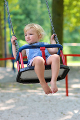 Cute preschooler girl having fun on a swing on summer day