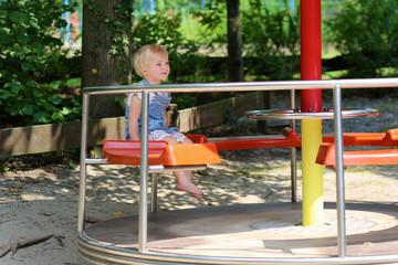 Cute preschooler girl having fun on playground in summer day