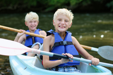 Two happy boys enjoying kayak on the river