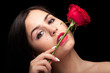 Beautiful woman with rose in hand on black