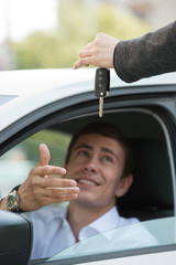 Salesman handing over keys car businessman