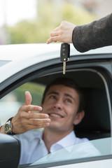 Salesman handing over keys car businessman