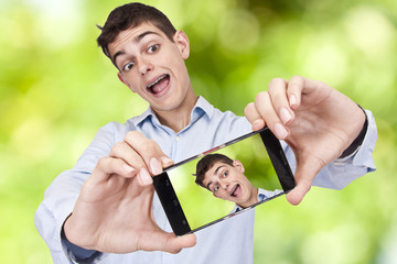 Young boy with phone becoming a self-portrait